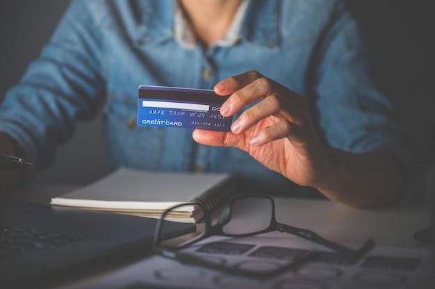 Cerca de la mano de la mujer usando laptop para comprar en línea o pagar con tarjeta de crédito. concepto de compras en línea.