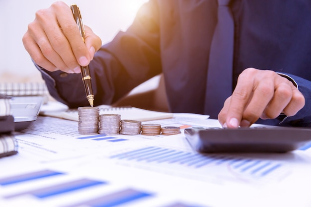 De cerca, la mano que pone el dinero monedas de pila en el ahorro de dinero y el concepto de negocio en crecimiento.