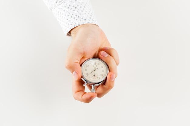 Cerca de la mano que sostiene el cronómetro