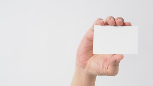 Cerca de la mano que sostiene la pequeña tarjeta vacía sobre fondo blanco.