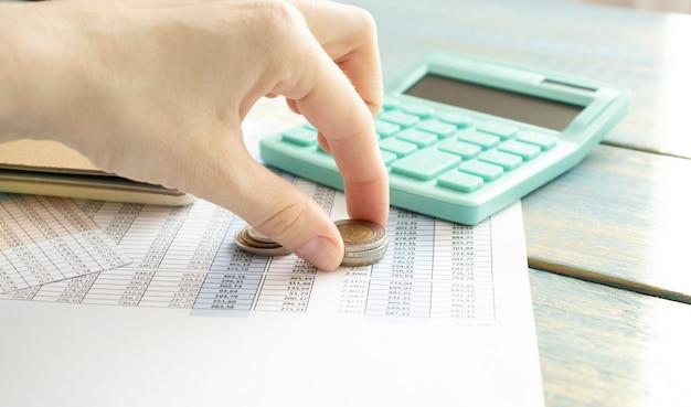 Cerca de la mano recogiendo monedas junto a una calculadora