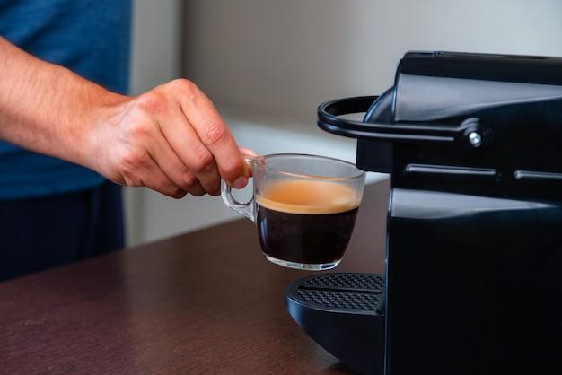 Cerca de la mano recogiendo una taza de café espresso de la máquina de café de cápsulas