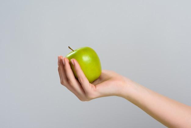 De cerca. la mano sostiene la manzana. nutrición apropiada.