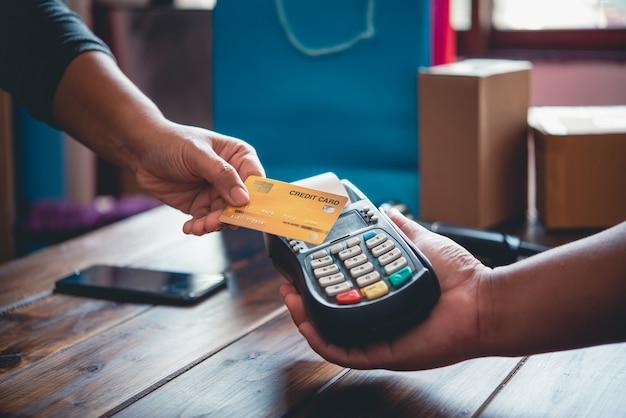 Cerca de la mano con tarjeta de crédito para pagar enviando la tarjeta de crédito al personal de la máquina de deslizamiento de tarjetas de crédito. pago en línea