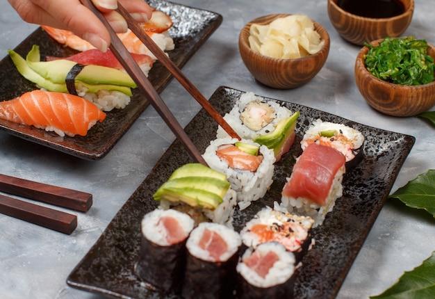 Cerca de la mano tomando rollo con palillos de un plato en la barra de sushi