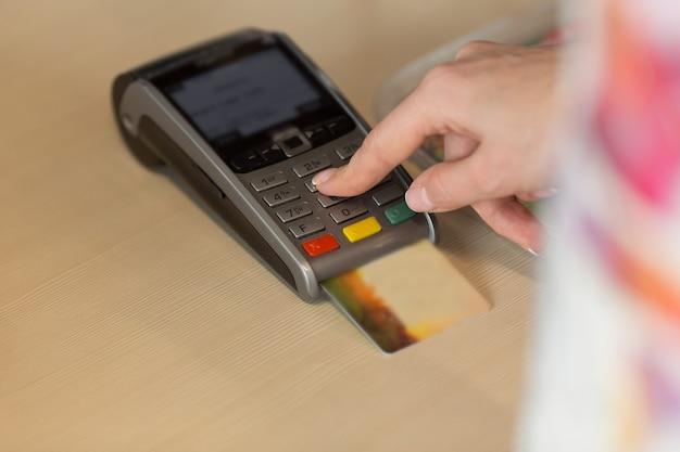 Cerca de la mano usando la máquina de deslizar la tarjeta de crédito para pagar. mano con tarjeta de crédito pase a través de terminal para pago en café. mujer ingresando el código de la tarjeta de crédito en la máquina deslizante.