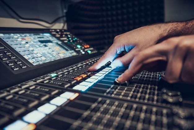 De cerca. manos ajustando el controlador de audio.