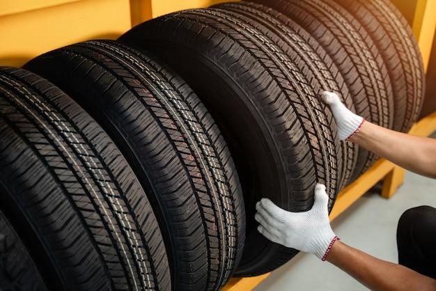 Cerca de las manos de un cambiador de neumáticos en un gran almacén de neumáticos para automóviles, portaequipajes con neumáticos para automóviles del cliente en el almacén de un distribuidor de neumáticos