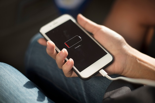 Cerca de las manos cargando teléfono móvil