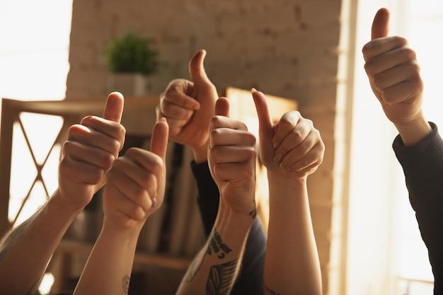 Cerca de las manos caucásicas masculinas y femeninas mostrando agradable, pulgares arriba