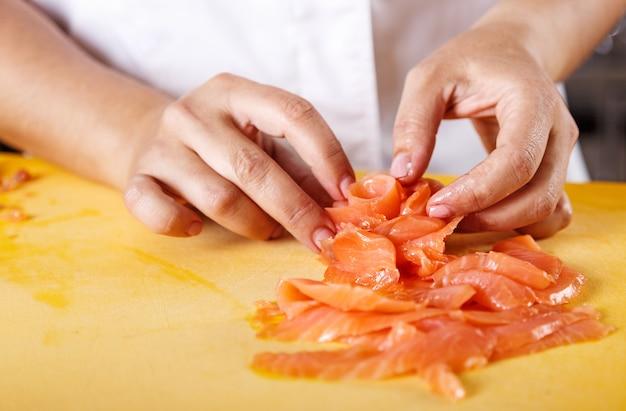 Cerca de las manos del chef para servir salmón en forma de flor en la cocina profesional
