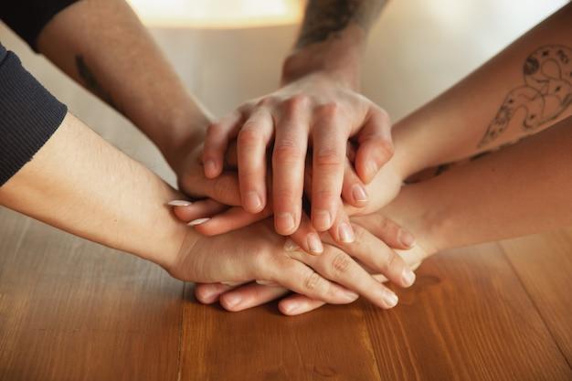 Cerca de las manos, cubriéndose unas a las otras