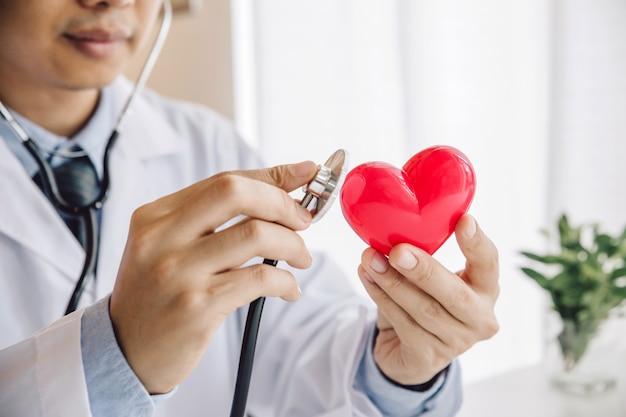 Cerca de las manos del doctor sosteniendo corazón rojo con estetoscopio
