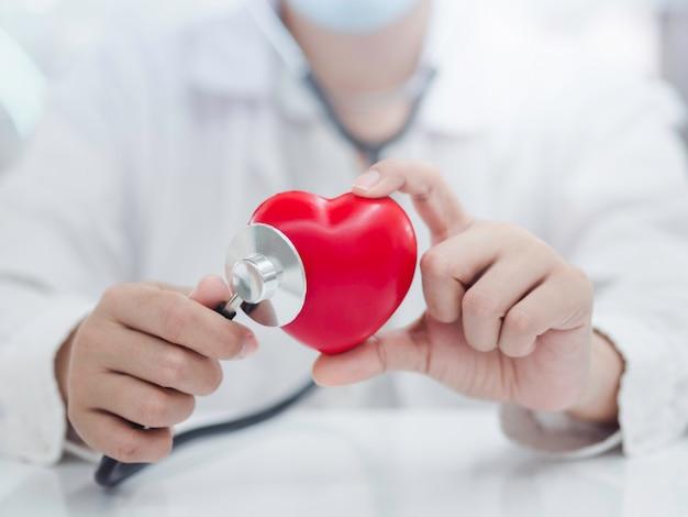 Cerca de las manos de la doctora examinando el corazón con un estetoscopio