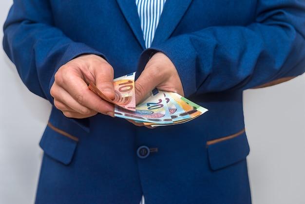 Cerca de manos de empresario contando billetes en euros
