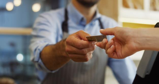 Cerca de las manos femeninas del comprador dando una tarjeta de crédito para pagar al vendedor masculino en la panadería. interior