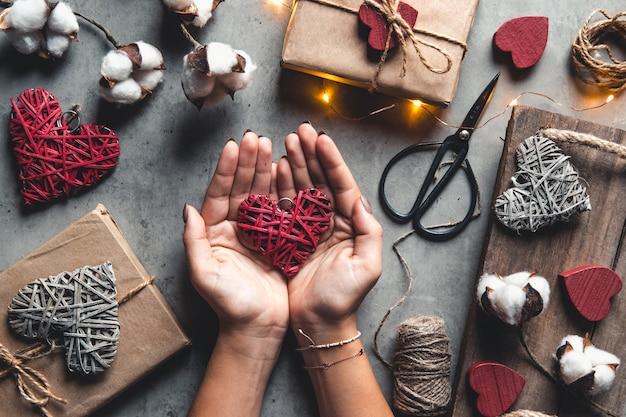 Cerca de manos femeninas sosteniendo un regalo en un corazón rosa presenta para el día de san valentín, cumpleaños, día de la madre. endecha plana. símbolo de amor. fondo del día de san valentín con cajas de regalo en tablero de hormigón.