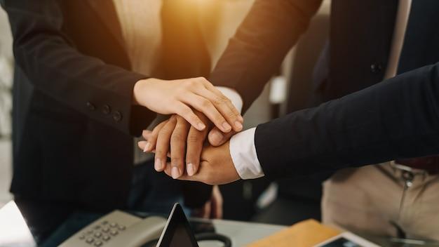 Cerca de las manos de la gente de negocios junta sus manos juntas en concepto de unidad en fooice