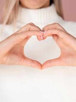 Cerca de manos gesticulando corazón