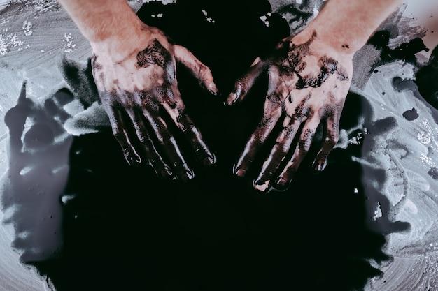 Cerca de las manos del hombre en pintura negra