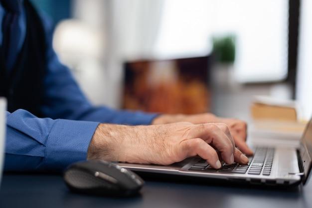 Cerca de las manos del hombre senior escribiendo