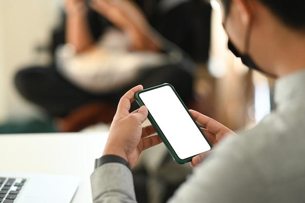 Cerca de las manos del hombre sosteniendo la pantalla en blanco del smartphone simulado mientras está sentado en la sala de reuniones