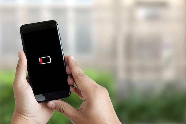 Cerca de las manos del hombre usando la batería del teléfono inteligente baja carga la pantalla de la batería