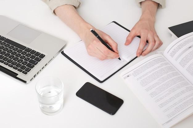 Cerca de las manos del joven escribiendo notas