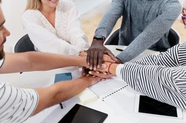 Cerca de las manos de los jóvenes colegas en una reunión