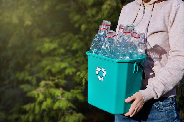 De cerca. las manos llevan una caja de plástico para reciclar. conciencia ambiental. salvando el planeta.