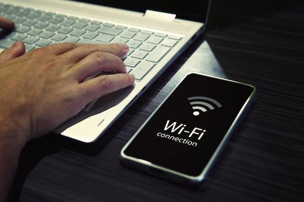 Cerca de manos masculinas escribiendo en el teclado de la computadora portátil y comprobando la conexión wi-fi del teléfono inteligente. teléfono móvil con icono de señal y palabras escritas conexión wi-fi en pantalla negra cerca de la computadora personal.