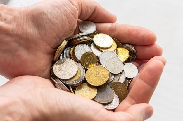 Cerca de manos masculinas llenas de monedas de plata y oro