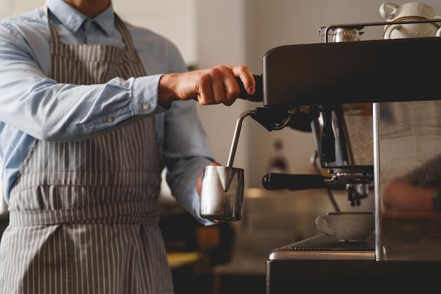 Cerca de manos masculinas sosteniendo la taza metálica plateada y vertiendo bebida caliente del grifo de la máquina de café