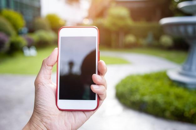 Cerca de manos masculinas sosteniendo el teléfono con pantalla negra aislada en el jardín