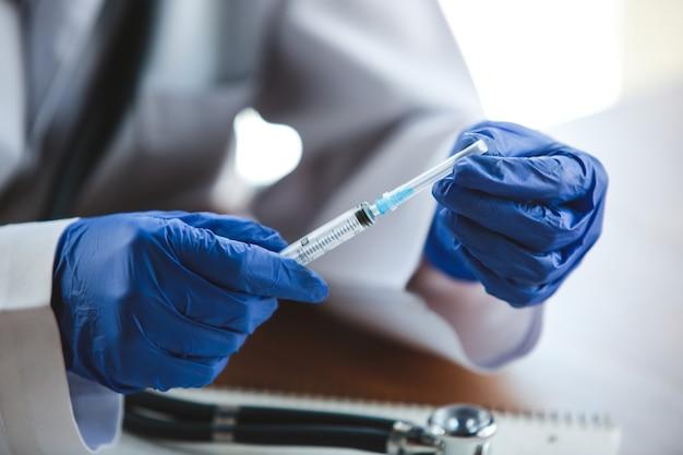 Cerca de las manos de los médicos con guantes protectores azules con estetoscopio y jeringa