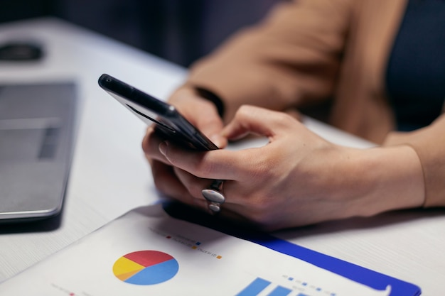 Cerca de las manos de la mujer emprendedora con teléfonos inteligentes en el transcurso de la fecha límite. la empresaria enviando mensajes de texto a altas horas de la noche mientras trabajaba en un proyecto importante con un teléfono inteligente.