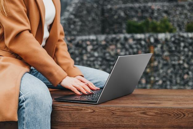 Cerca de las manos de una mujer escribiendo en una computadora portátil en la calle contra un edificio de oficinas. distancia de trabajo empresaria