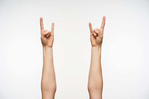 Cerca de las manos de la mujer joven mostrando gesto de heavy metal y rock