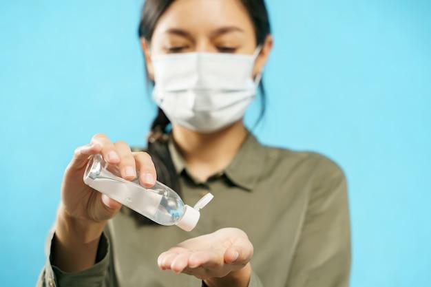 Cerca de manos de mujer en máscara protectora médica con gel desinfectante sobre fondo azul.