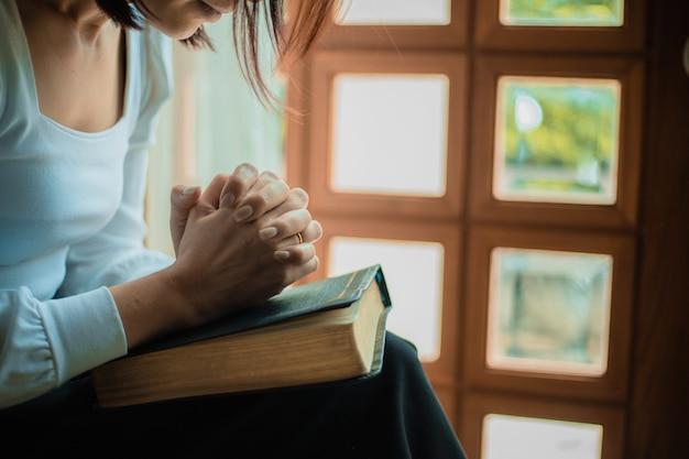 Cerca de las manos de la mujer rezando en la iglesia, la mujer cree y reza a dios.
