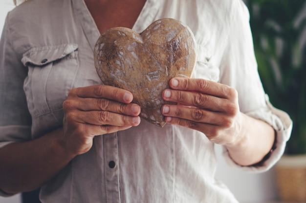 Cerca de manos de mujer sosteniendo corazón de madera. concepto de prevención de ataques cardíacos y cuidado de personas sanas. personas hembras maduras en el interior