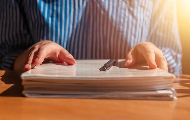 Cerca de las manos de las mujeres con una pila de documentos en papel en un escritorio de madera