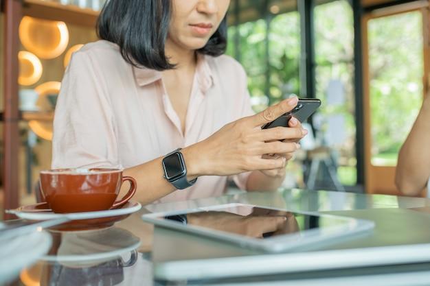 Cerca de las manos de las mujeres sosteniendo el teléfono móvil con pantalla de espacio de copia en blanco para su mensaje de texto publicitario o contenido promocional, noticias de lectura femenina en el teléfono celular durante el descanso en la cafetería