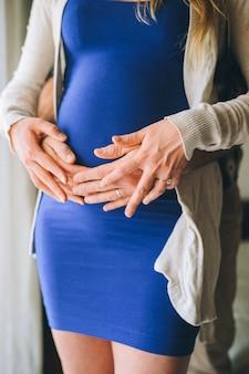 Cerca de las manos de los padres tocando el vientre embarazado en casa