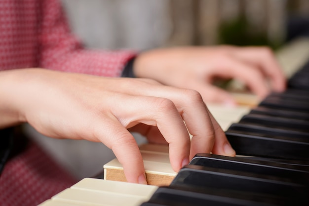 Cerca de las manos de una pequeña niña con talento tocando el piano en casa