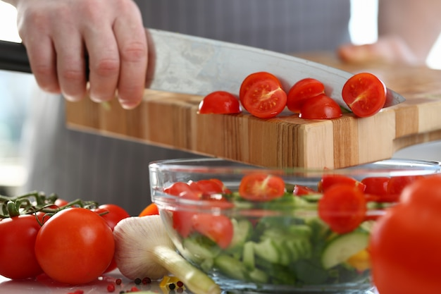 Cerca de las manos que agregan tomates en una ensaladera