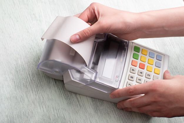 Cerca de manos rasgando un cheque de una caja registradora después de comprar un producto