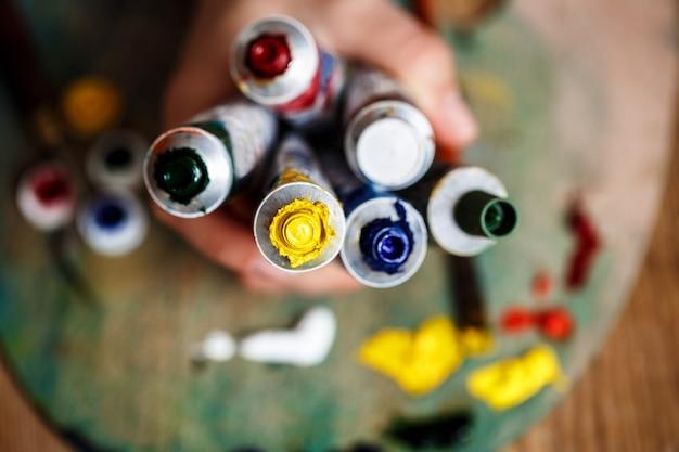 Cerca de manos sosteniendo pinturas al óleo, pared de paleta