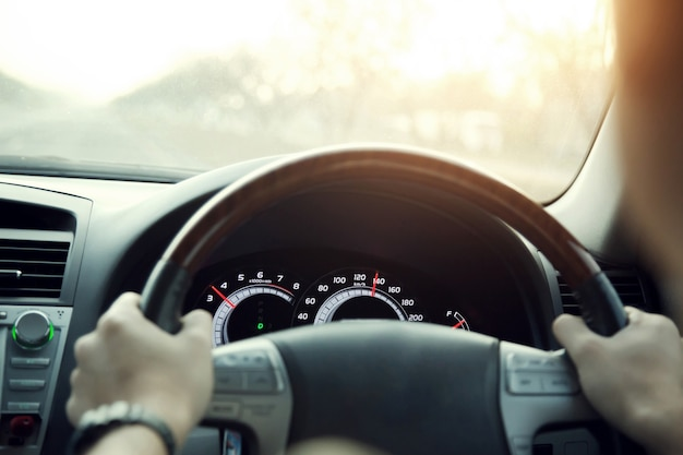 Cerca de las manos sostienen el volante joven conduciendo un coche en la carretera. viaje del conductor del viaje.