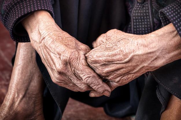 Cerca de las manos de la vieja persona no identificada